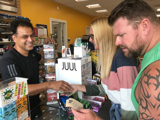 Kevin Dugan checks his lottery tickets while wife Andrea receives change from K.D. Sune, co-owner of Gud2Go convenience food store that relocated after the Valero service station storeit leased was demolisihed.