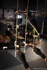 People inside Bircus Brewery in Ludlow watch trapeze performers dangle above their heads on a rope swing.