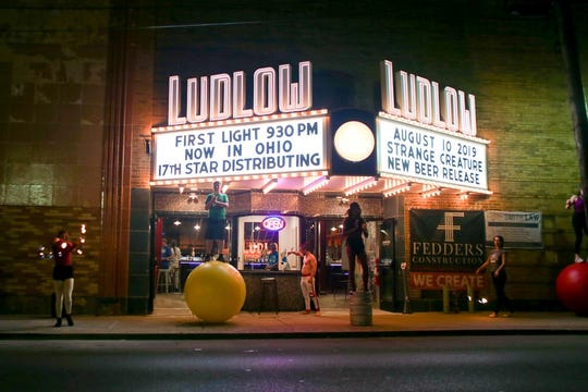 Jugglers and other circus performers beckon people inside Bircus Brewery the night the replica Ludlow Theater marquee was lit up for the first time Aug. 10.