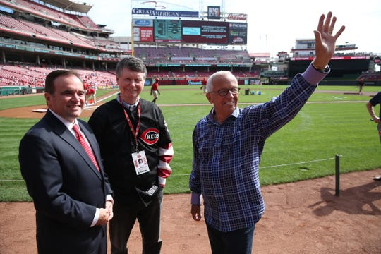 Cincinnati Reds Hall of Fame broadcaster Marty Brennaman waves to the crowd as he takes the field with Cincinnati Mayor John Cranley, left, and Bill Cunningham for his last day of broadcasting for the Reds at Great American Ball Park  Thursday, September 26, 2019.