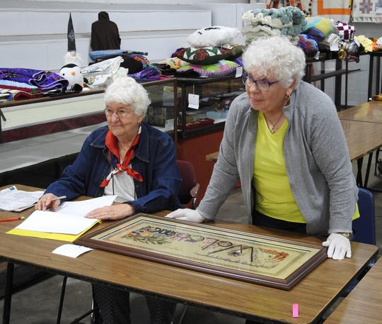 Dorothy Dalton, Art Hall worker, with needlework judge Ruth Treen Thursday in the Art Hall at the Coshocton County Fair.