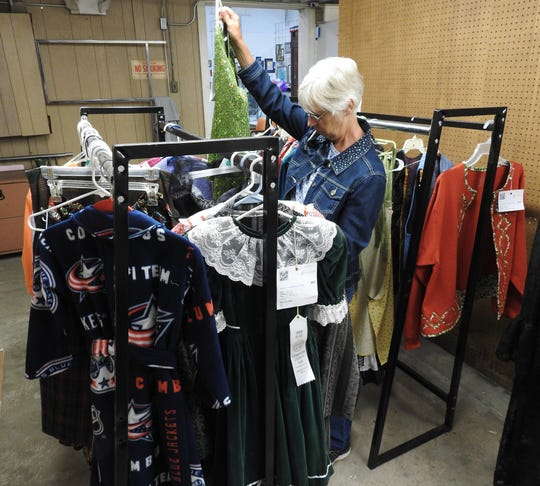 Sewing judge Vicki Bechtel of Fredericktown reviews handmade clothes Thursday in the Art Hall at the Coshocton County Fair.
