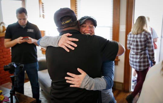 Jennifer Sherrill, a sergeant first class at the Iowa Army National Guard, gets a hug as she is welcomed to her new home on Thursday, Sept. 26, 2019, in Des Moines. In honor of Sgt. Sherrill's service, the home was renovated and given to her mortgage-free by the Veterans Association of Real Estate Professionals, in partnership with Bank of America.