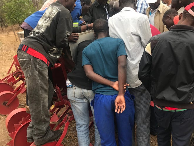 Farmers in Mozambique learn about a corn planter.