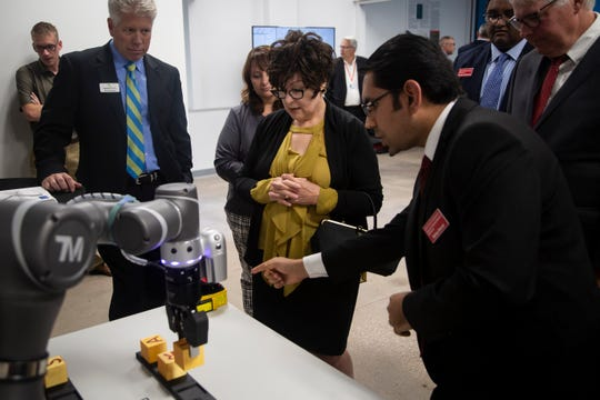 Debi Durham, director of the Iowa Economic Development Authority watches a robot work during the opening of ISU's digital manufacturing lab, CIRAS, on Thursday, Sept. 26, 2019 in Ames. The center was funded with a $100,000 contribution from Alliant Energy and $250,000 from the Iowa Economic Development Authority.ISU digital manufacturing lab opening on Thursday, Sept. 26, 2019 in Ames.