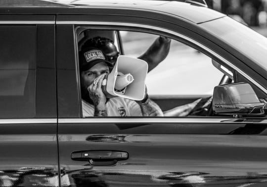 A man shouts support from a megaphone for UAW members on strike against General Motors outside of Flint Assembly while driving along Van Slyke Rd. in Flint on Tuesday, September 24, 2019