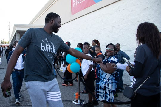 Draymond Green fist bumps fans in line during the grand opening of Blink Fitness in Redford Township, Thursday, Sept. 26, 2019.