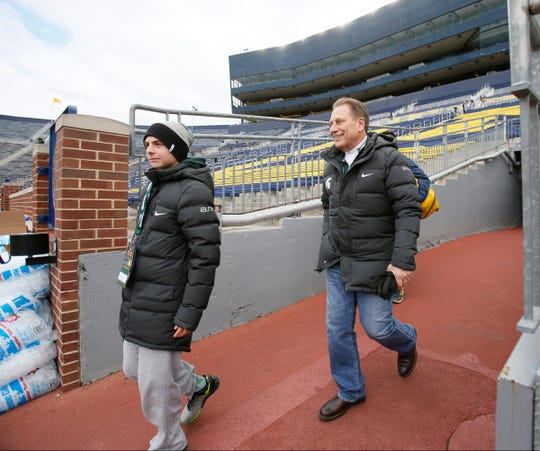 Steven Izzo and his father, Michigan State coach Tom Izzo, walk through the tunnel and onto the field at Michigan Stadium on Saturday, Oct. 17, 2015.
