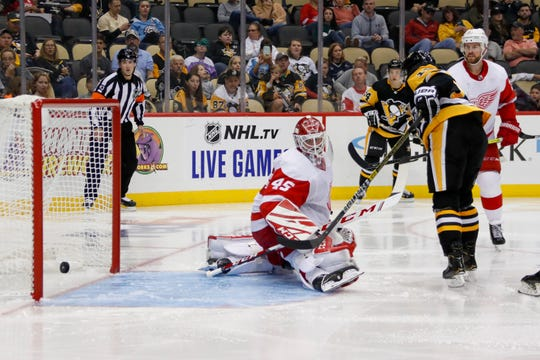 Pittsburgh Penguins' Bryan Rust, right, scores on Detroit Red Wings goaltender Jonathan Bernier during the second period of an NHL preseason hockey game, Wednesday, Sept. 25, 2019, in Pittsburgh.