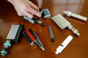 In this Tuesday, April 10, 2018 photo, a high school principal displays vaping devices that were confiscated from students at the school in Massachusetts. On Thursday, Sept. 26, 2019, the Centers for Disease Control and Prevention said 805 confirmed and probable cases have been reported to have a vaping-related breathing illness, and the death toll has risen to 12.