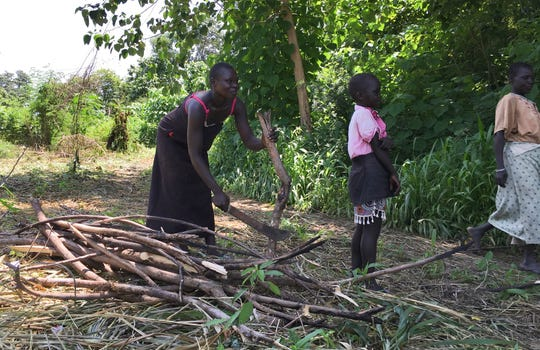 FILE - In this Friday, July 14, 2017 file photo, a woman chops down trees for firewood with her daughter in the small town of Rajaf, near Juba, in South Sudan.