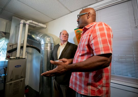 Jose Guzman, right, shows Detroit Mayor Mike Duggan his new HVAC system.  The home is the first of 200 houses being upgraded with new windows, HVAC systems and insulation to lessen the noise and environmental pollution of the construction and use of the Gordie Howe bridge.