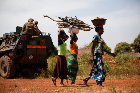 FILE - In this Monday, Feb. 10, 2014 file photo, women carrying wood walk past a French military patrol 10 kms south of Yaloke, north of Bangui, in Central African Republic.