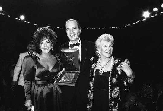 American film star Elizabeth Taylor, left, is presented with a medal of the City of Paris by Paris Mayor Jacques Chirac during a gala soiree in a Paris night club at night to benefit AIDS research on Nov.26 1985.