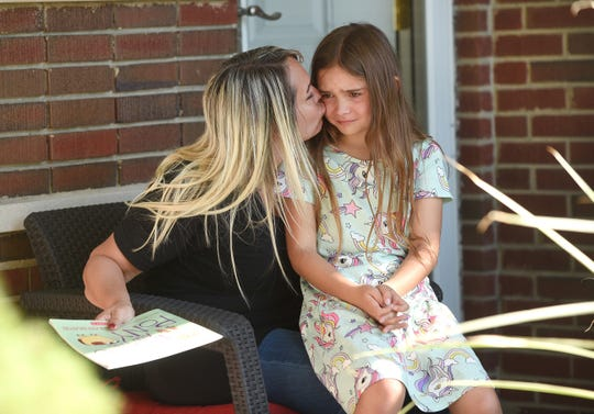 Angela Shock kisses her daughter Racquel, 8, who senses the concern of her parents  Thursday at their Warren home.  The UAW strike has hit the finances of the Shock household as Angela and her husband Jon both work for General Motors.