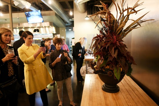 Attendees take photos of the porch decoration created by Laurie Bolach, not shown here, of Olive's Bloombox at the Homestyle Harvest Dish and Design event at the Great Lakes Culinary Center in Southfield on Sept. 25, 2019.