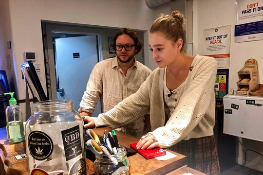 In this photo taken Sept. 20, 2019, David Alport, owner of the Bridge City Collective marijuana dispensary in Portland, Ore., goes over sales numbers with the store's general manager Cameron Moore. The company has seen a 31% decrease in its sales of vaping products in the past two weeks.