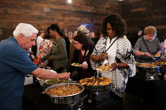 Vickie Williams of Southfield, right, gets some of the appetizers at by Chef Reva Constantine at the Homestyle Harvest Dish and Design event at the Great Lakes Culinary Center.