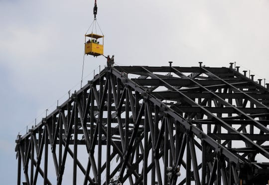 Workers reach for a transport vehicle lowered to their position at the very top the roof structure currently under construction atop Globe Life Field as a light rain falls in Arlington, Texas in July.