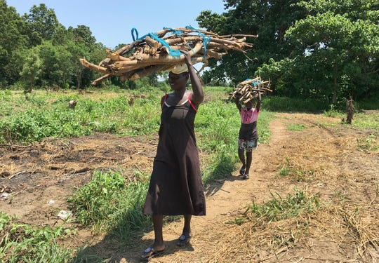 FILE - In this Friday, July 14, 2017 file photo, a woman and her daughter walk home with firewood in the small town of Rajaf, near Juba, in South Sudan.