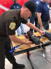 An officer in crisis intervention training learns bleeding control on a fake leg.