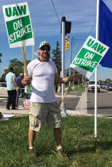 Mike Frost of Highland Township joked that a second picket sign kept him balanced as he walked the line at the GM Tech Center's Gate 10.