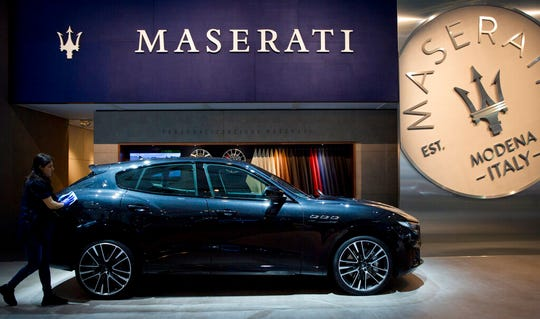 In this Jan. 18, 2019 file photo a worker polishes the new Maserati Levante during the opening of the Brussels Auto Show. The carmaker owned by Fiat Chrysler Automobiles announced production and electrification roll-outs as part of plans announced last year to invest 5 billion euros in Italian production from 2019-2022.
