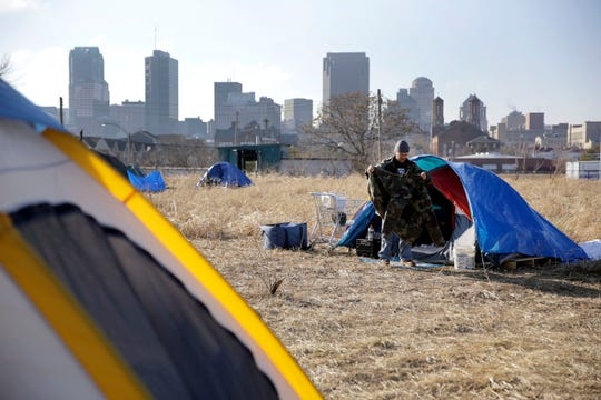 A man cleans out his tent at a large homeless encampment, near downtown St. Louis.