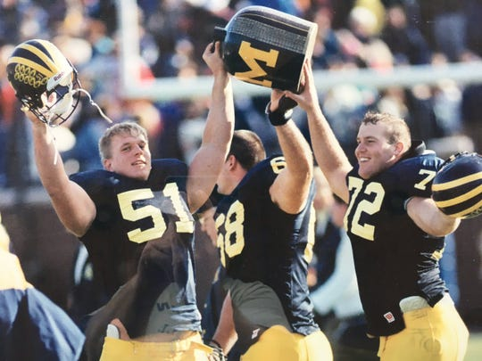 Michigan offensive lineman Doug Skene, right, celebrates a victory over Minnesota in the Little Brown Jug game.