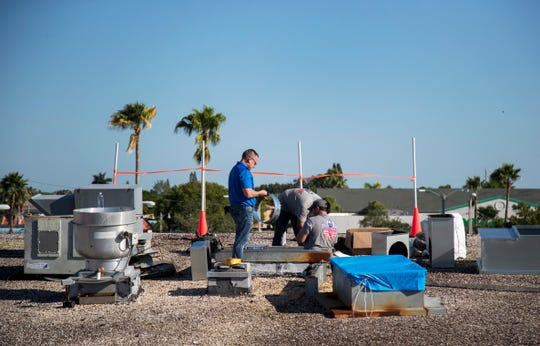 William Barnes, left, Abel Ortiz and Chris Worden, right, of Ellsworth's Heating & Cooling prepare to install a new air conditioning unit on the roof of the Southwest Florida Military Museum & Library on Wednesday, September 25, 2019, in Cape Coral.  The new AC unit was donated by Ellsworth's and installed for free. A new compressor for the building's main AC unit was also donated and installed for free by TWC Services and Conditioned Air employees.