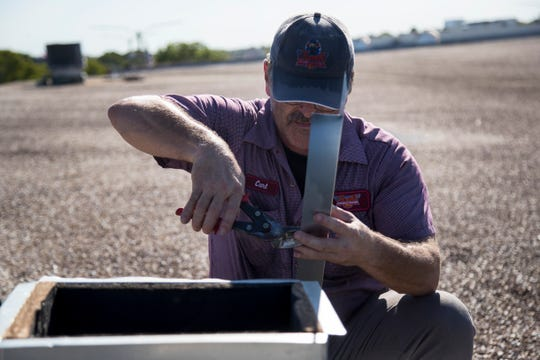 Carl Pinault of Ellsworth's Heating & Cooling works on a base for new air conditioning unit on the roof of the Southwest Florida Military Museum & Library on Wednesday, September 25, 2019, in Cape Coral.