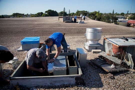 Chris Worden, left, and William Barnes of Ellsworth's Heating & Cooling prepare to install a new air conditioning unit on the roof of the Southwest Florida Military Museum & Library on Wednesday, September 25, 2019, in Cape Coral.  The new AC unit was donated by Ellsworth's and installed for free. A new compressor for the building's main AC unit was also donated and installed for free by TWC Services and Conditioned Air employees.
