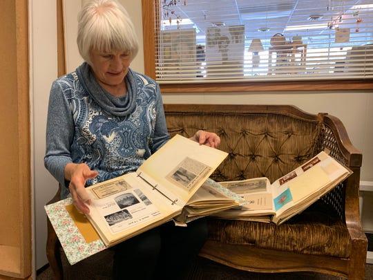 Judy Ericksen flipping through the scrapbooks at Gallery 16 to show and explain the gallery's history.