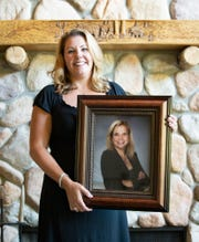 """Former owner of Hare Chevrolet, and one half of the """"Sisters of Savings,"""" Monica Peck, holds a photograph of her sister, Courtney Cox Cole."""