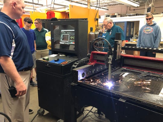 """South-Doyle High School senior Lennox Granath looks on as teachers Jim Thomas and Jeff Bryant use the Lincoln Torchmate plasma cutter machines to cut a metal sign on Sept. 24. """"I have about 20 students in my class,"""" said Bryant, architectural & engineering design teacher. """"We have to recruit –they aren't required to take CTE classes; they have to choose them."""""""
