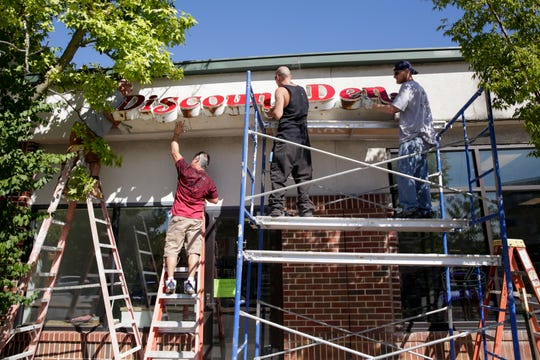 Workers hang the Discount Den sign above the entrance to their new location, 618 W Stadium ave., Thursday, Sept. 26, 2019, in West Lafayette.