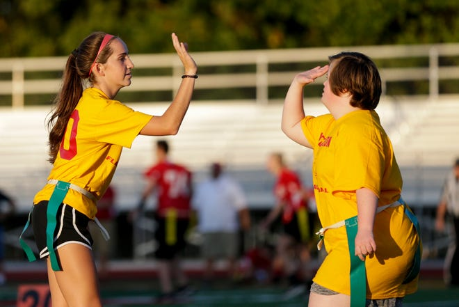 McCutcheon's Megan Merryman (10) reaches out to high five McCutcheon's Kaleigh Singer (7) during an IHSAA unified flag football game, Wednesday, Sept. 25, 2019, at McCutcheon High School in Lafayette.