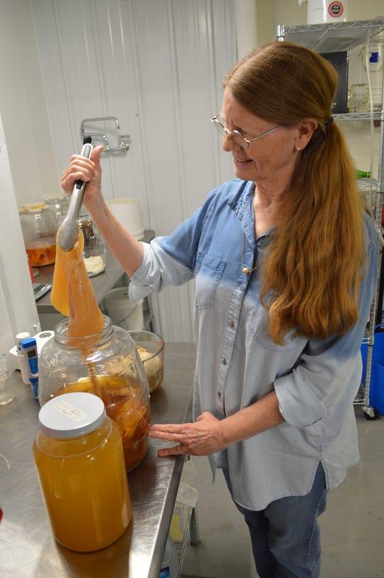 Rosanna Czarnecki strains kombucha at her food lab R2 Positive Culture