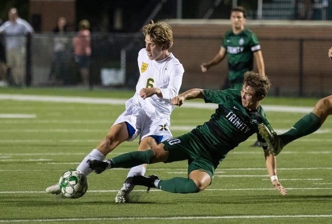 Sulli Meyer tries to edge past Jeremy Mason's reach as the Tigers and Shamrocks battle Wednesday, Sept. 25, 2019 in Louisville, Ky. St. X soccer beat Trinity 1-0 scoring late in the second half.