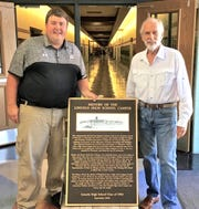 Lincoln High School Class of 1964 recently presented a plaque to the school commemorating the 100th anniversary of the Board of Education's decision to build the school's campus. Pictured is the plaque being given to Principal Lee Thennes.