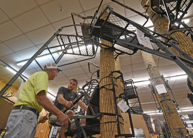 Jake Hummel of the Sportsman's Den in Shelby demonstrates a tree stand to Paul Schroeder on Wednesday afternoon.