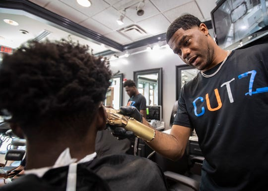 Memphis Tigers guard, Damion Baugh (10), gets his hair cut by Shun Smith at The Cutz in Wolfchase Galleria, Sunday, Sept. 15, 2019.