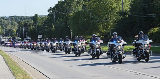 Police motorcycles led the funeral procession for Officer Mark Lentz as it headed north along South Barker Road from Elmbrook Church.