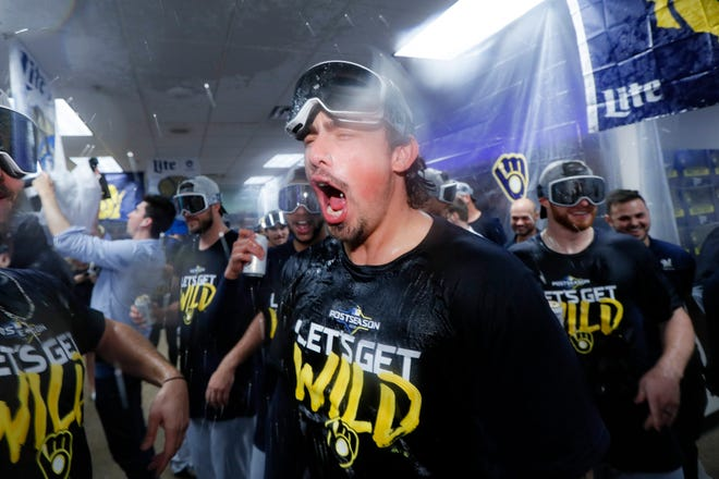 The Brewers celebrate in the visitors' clubhouse after beating the Reds, 9-2, Wednesday night to clinch a playoff berth for the second consecutive season.