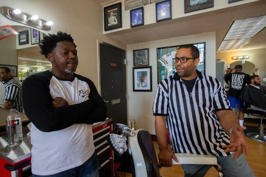 Kwabena Antoine Nixon, left, listens as his barber since 2004, Richard Armstead, talks about the importance of developing strong ties with clients at Gee's Clippers.