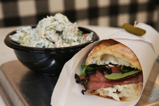 Among the baguette sandwiches at Press. au marché, 207 E. Buffalo St., is the pastrami with cracked-pepper mayonnaise and pickled peaches. The sandwiches are wrapped in paper and speared with a cornichon. Beside the sandwich is the cafe's potato salad with dill.