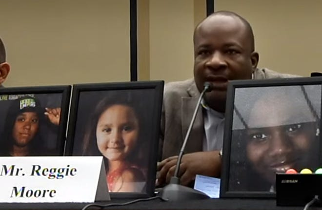 """Milwaukee Health Department Office of Violence Prevention Director Reggie Moore testifies Thursday before a Congressional subcommittee that gathered to hear about community responses to gun violence. In front of him were photographs of some of Milwaukee's gun violence victims: 20-year-old Quanita """"Tay"""" Jackson, 5-year-old Laylah Petersen, and 13-year-old Sandra Parks."""