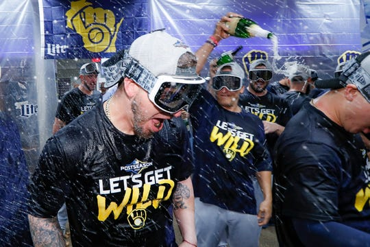 Yasmani Grandal and the rest of his teammates celebrate after the Brewers clinched a playoff berth with a 9-2 win over the Reds.