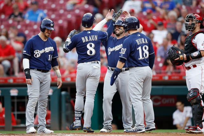 Ryan Braun  celebrates with teammates after hitting a grand slam home run in the first inning.