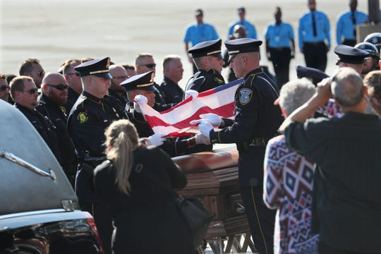 The honor guard folds the flag above the casket of Milwaukee Police Officer Mark Lentz. His funeral was held at Elmbrook Church in Brookfield.